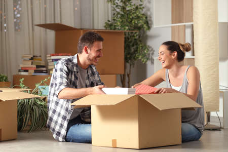 Happy couple laughing unboxing belongings moving house sitting on the floor in the night Stock Photo