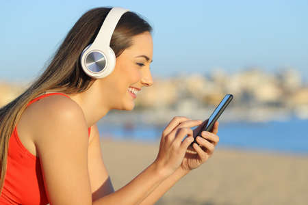 Profile of a happy woman in red listening to music using cell phone on the beach Archivio Fotografico - 125066457