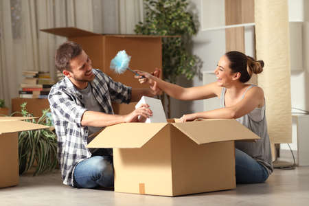 Happy couple joking with a duster clean unboxing belongings moving home