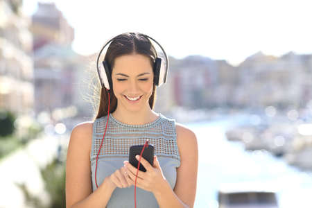 Front view of a girl listening to music choosing online songs in a coast town Archivio Fotografico - 125066471