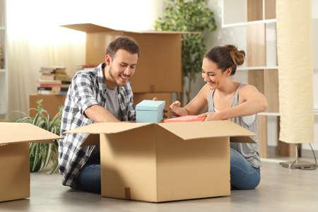 Glückliches Paar, das seine Sachen auspackt und nach Hause auf dem Boden sitzt