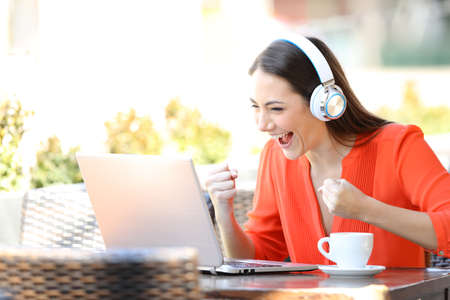 Excited woman wearing headphones watching and listening media on laptop in a coffee shop