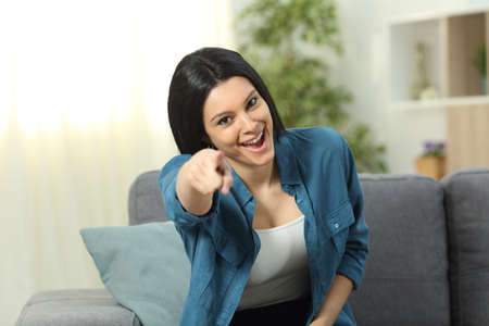 Happy woman pointing at camera sitting on a couch in the living room at home