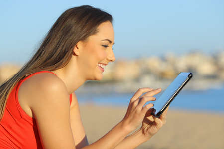 Profile of a happy woman browsing tablet online content on the beach Archivio Fotografico - 125066510