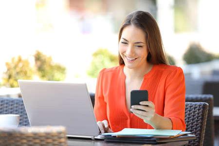 Happy entrepreneur using multiple electronic devices sitting in a coffee shop terrace Reklamní fotografie