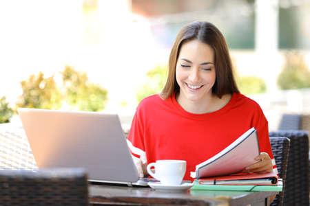 Studente felice con un computer portatile che studia le note di lettura seduto in una terrazza di una caffetteria