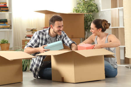 Happy couple unboxing belongings moving house sitting on the floor Stock Photo