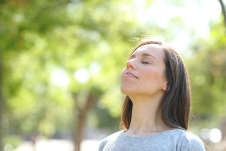 Relaxed woman breathing deep fresh air standing in a green park or forest Standard-Bild