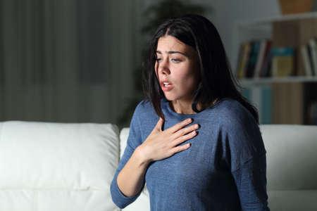 Vrouw lijdt aan een angstaanval alleen 's nachts op een bank thuis