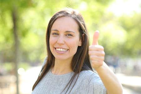 Mujer feliz mirando a la cámara con los pulgares para arriba de pie al aire libre en un parque