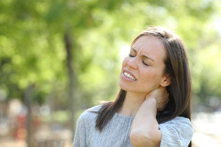 Stressed woman suffering neck ache standing outdoors in a park Stock Photo