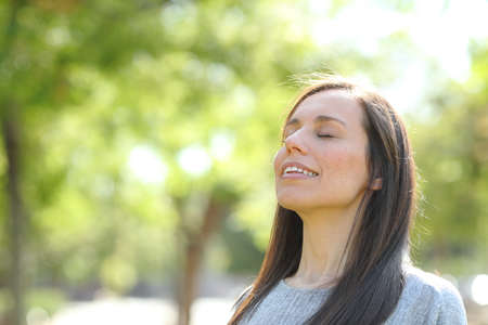 Happy woman breathing fresh air standing in a green park or forest