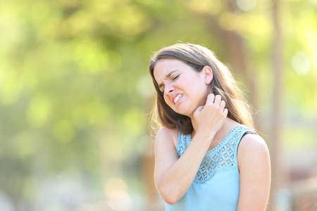 Donna che soffre di prurito graffiare il collo in piedi all'aperto in un parco Archivio Fotografico