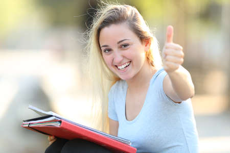 Happy student with thumbs up looks at camera sitting outdoors in a park
