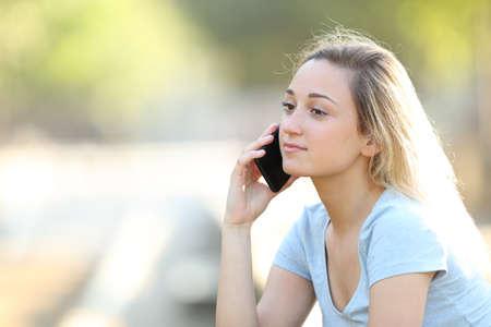 Adolescente sérieuse parlant au téléphone intelligent se reposant dans un parc Banque d'images