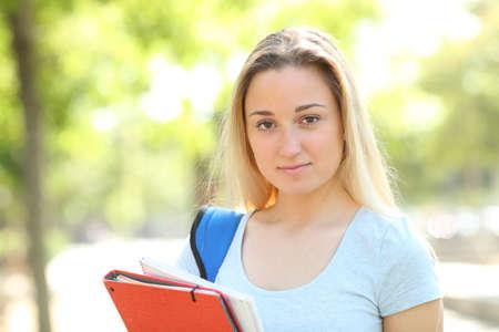 Ernsthafte Teenager-Studentin, die in einem Park in die Kamera schaut Standard-Bild