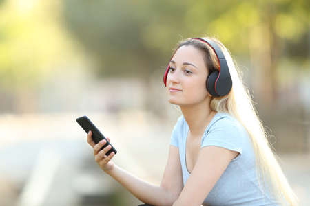 Relaxed girl listening to music with headphones and smart phone looking away sitting in a park Stock Photo