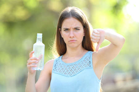 Angry woman holding a plastic bottle with thums down in a park with a green background 版權商用圖片