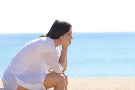 Profil einer besorgten Frau, die im Sommer auf einer Bank am Strand sitzt