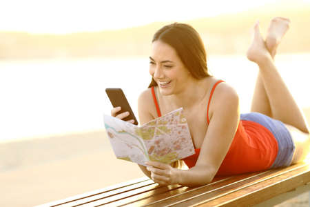 Full body portrait of a happy tourist checking smart phone and paper guide lying on a bench on the beach on summer vacation
