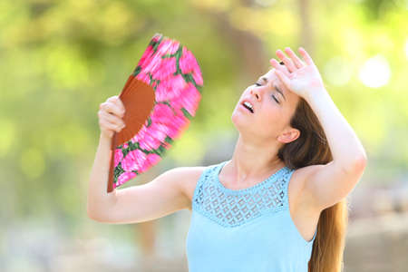 Woman complaining suffering heat stroke on summer on green background in a park