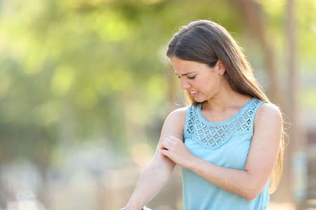 Vrouw krabt aan arm omdat het prikt in een park met een groene achtergrond