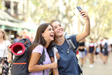 Two happy backpackers taking selfies with a smart phone in the street on vacation Stock Photo