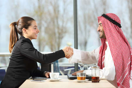 Side view portrait of an arab businessman and businesswoman handshaking in a coffee shop or hotel bar