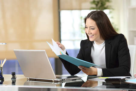Happy businesswoman checking paper informs sitting at office