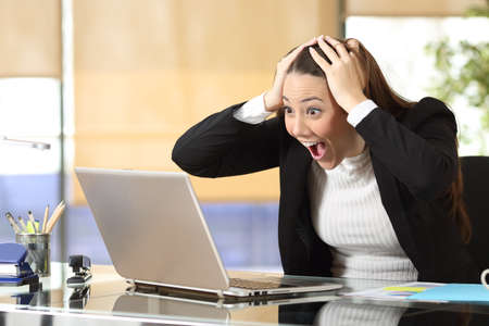 Excited businesswoman checking laptop online content reading good online news at office