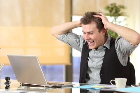 Aufgeregter Geschäftsmann, der Laptop-Inhalte überprüft und gute Nachrichten im Büro liest Standard-Bild
