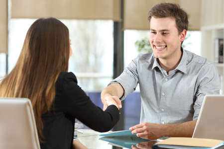 Happy businesspeople handshaking after negotiation at office Stock Photo