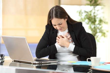 Jonge zakenvrouw met pijn op de borst die alleen op kantoor zit