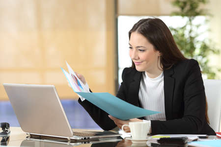 Serious businesswoman checking paper informs sitting at office Foto de archivo