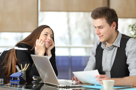 Candid young businesswoman falling in love with a colleague at office Stock Photo