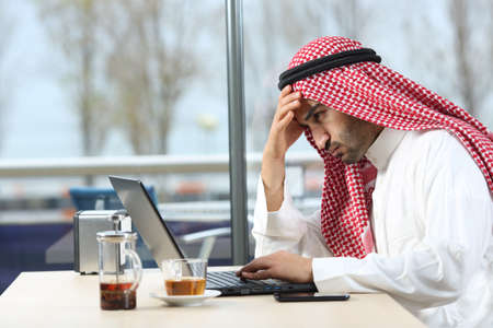 Confused arab man checking laptop content sitting in a coffee shop