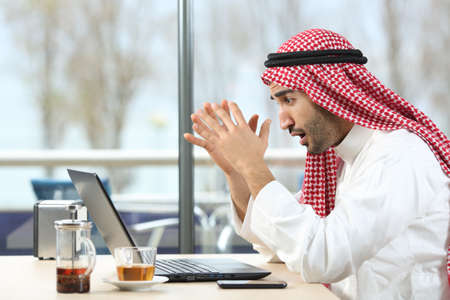Shocked arab man checking laptop content sitting in a coffee shop Stockfoto