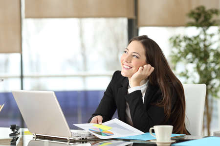 Happy office worker dreaming looking at side with copy space