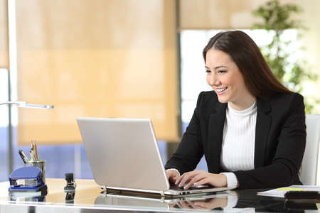 Happy businesswoman writing on laptop sitting at office