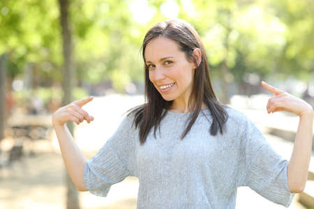 Proud woman pointing herself with both hands standing in a park