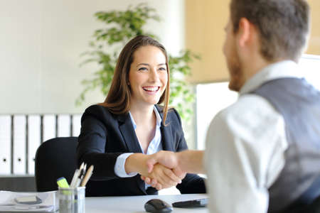 Happy businesspeople handshaking after deal or interview at office Imagens