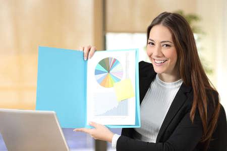 Feliz empresaria mostrando documento en papel en blanco a la cámara en la oficina Foto de archivo