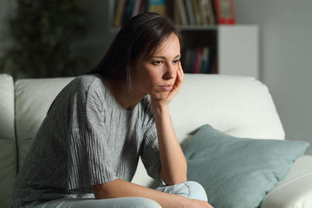 Serious pensive woman looks away in the night sitting on a couch in the living room at home Stock Photo