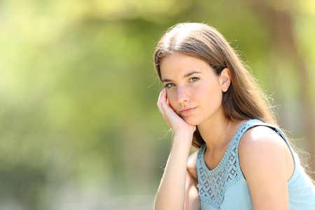 Retrato de una mujer seria belleza mirando a la cámara en un parque con un fondo verde
