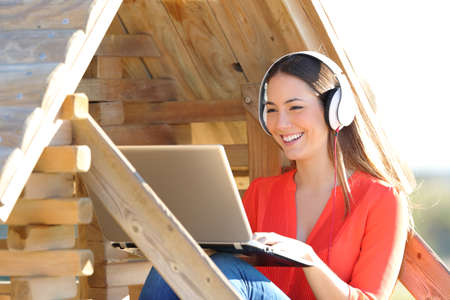 Happy woman using laptop and headphones watching media in a wood house