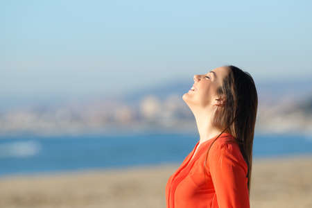 Side view portrait of a happy woman in orange breathing fresh air on the beach in a sunny day