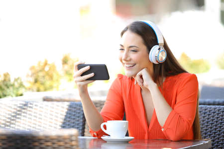 Happy woman watching media on smart phone sitting in a restaurant terrace