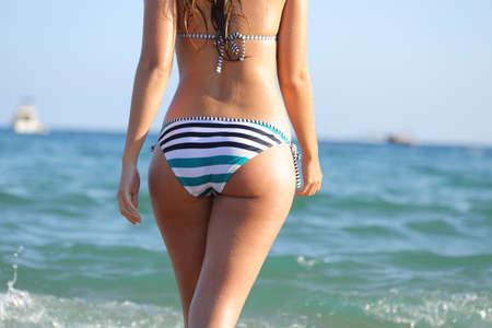 Vue arrière d'une fille en bikini prête à se baigner sur la plage en vacances d'été