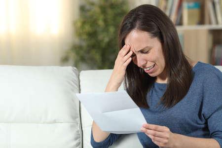 Traurige Frau, die einen Brief liest, der zu Hause auf einer Couch im Wohnzimmer sitzt