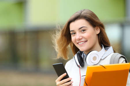 Happy student posing looking at camera holding smart phone and headphones in the street Stock Photo